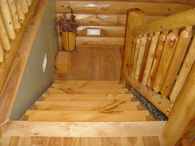 Black Ash stair landing installed by owner in this log cabin lake home near Grand Rapids, MN